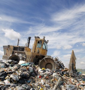 A bulldozer on a messy landfill pile of rubbish